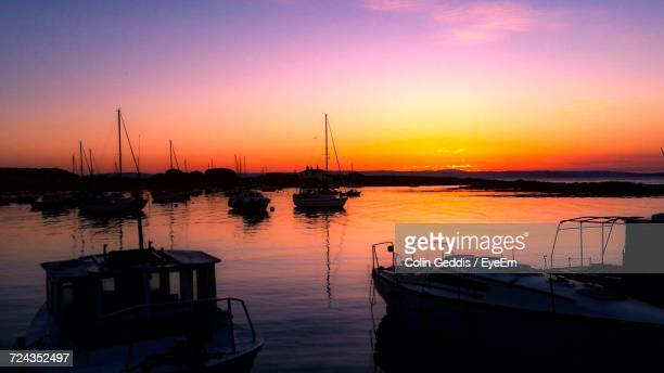 Silhouette Boats Moored At Harbor Against Sky During Sunset