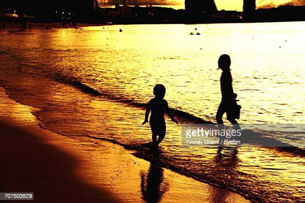 Silhouette Boy And Girl Playing On Shore At Beach During Sunset