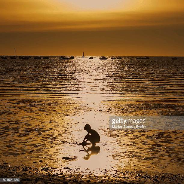 Silhouette boy playing in sea at sunset