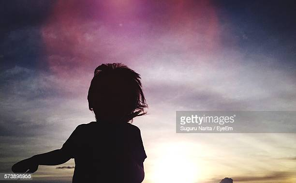 Silhouette Boy Standing Against Sky During Sunset
