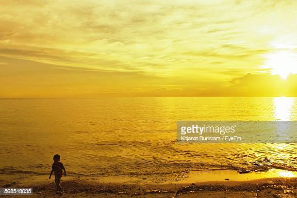 Silhouette Boy Walking On Shore Against Yellow Sunset Sky