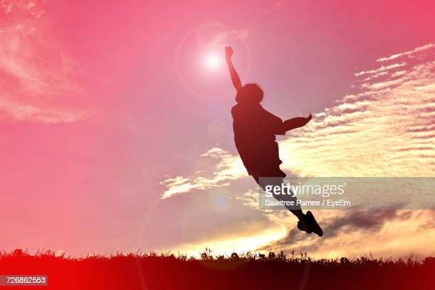 Silhouette Boy With Arm Raised Levitating Against Sky During Sunset