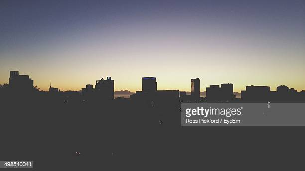 Silhouette buildings against clear sky at sunrise