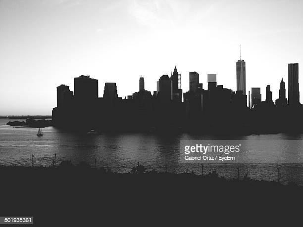 Silhouette buildings against clear sky with river in foreground