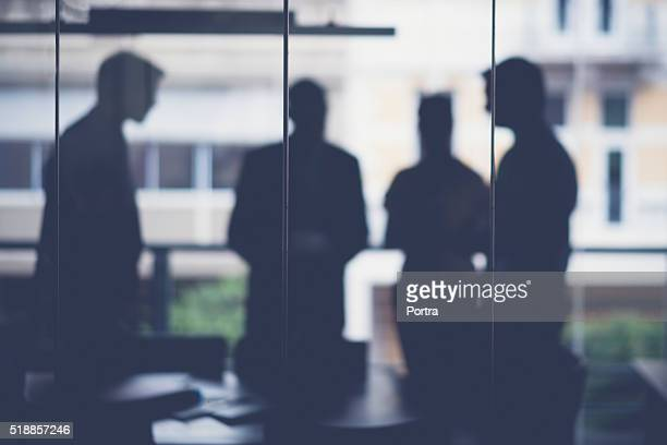 Silhouette business people discussing in meeting room