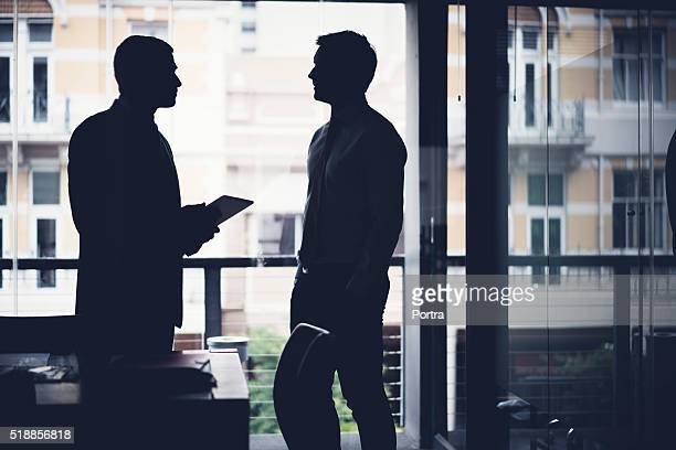 Silhouette businessmen discussing in dark office