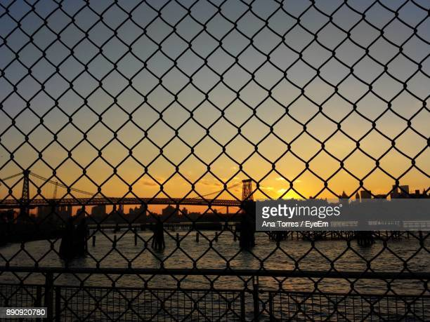Silhouette Chainlink Fence By River Against Sky During Sunset