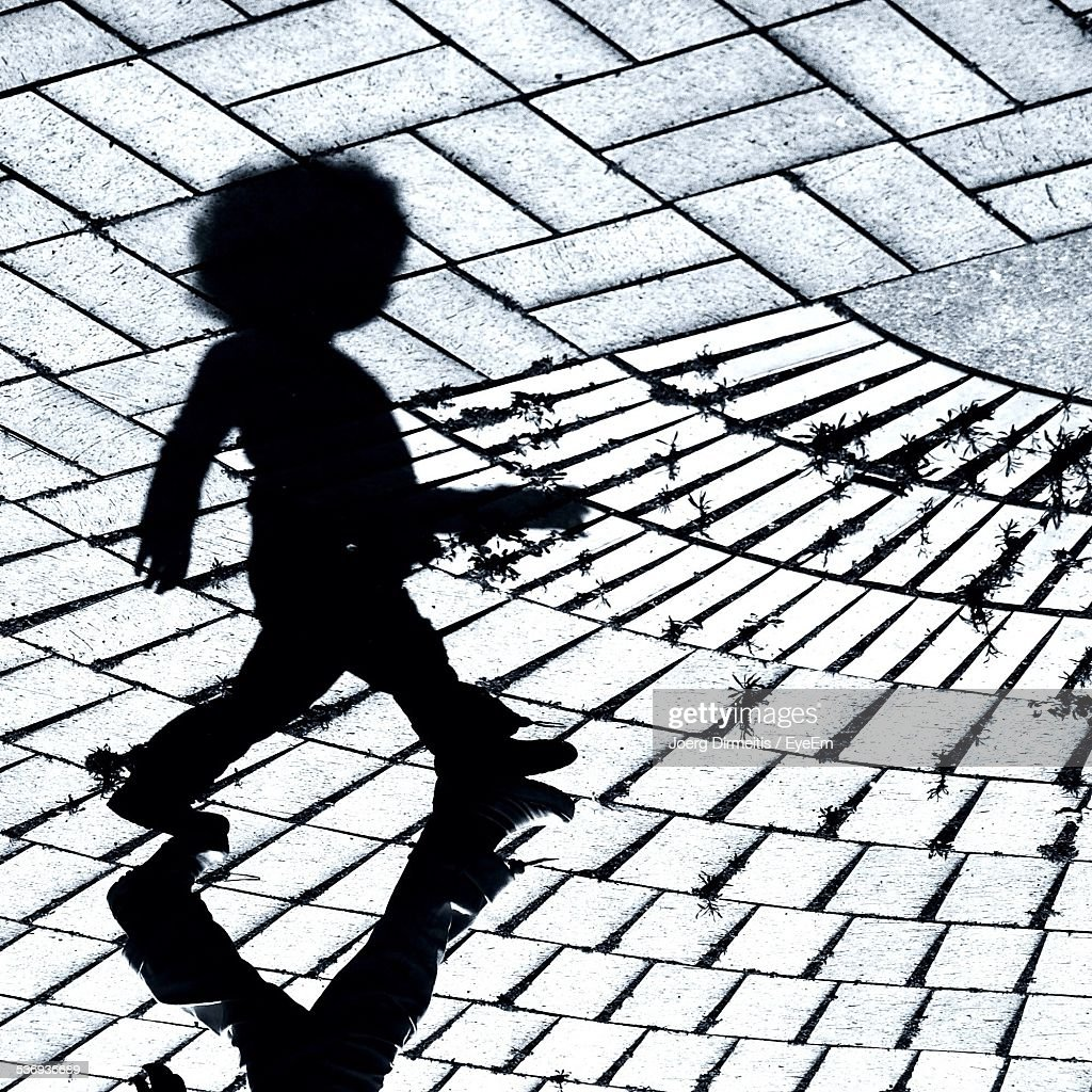 Silhouette Child Walking On Footpath On Sunny Day