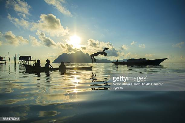 Silhouette Children Playing On Sea During Sunset