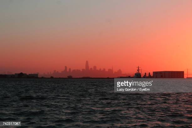 Silhouette City By Sea Against Clear Sky During Sunset