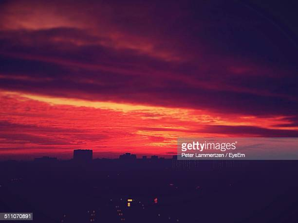 Silhouette cityscape against dramatic sky at sunset