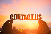 silhouette of hand take contact us word with sunshine