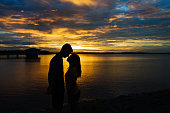 Silhouette couple in love at lake during beautiful sunset.