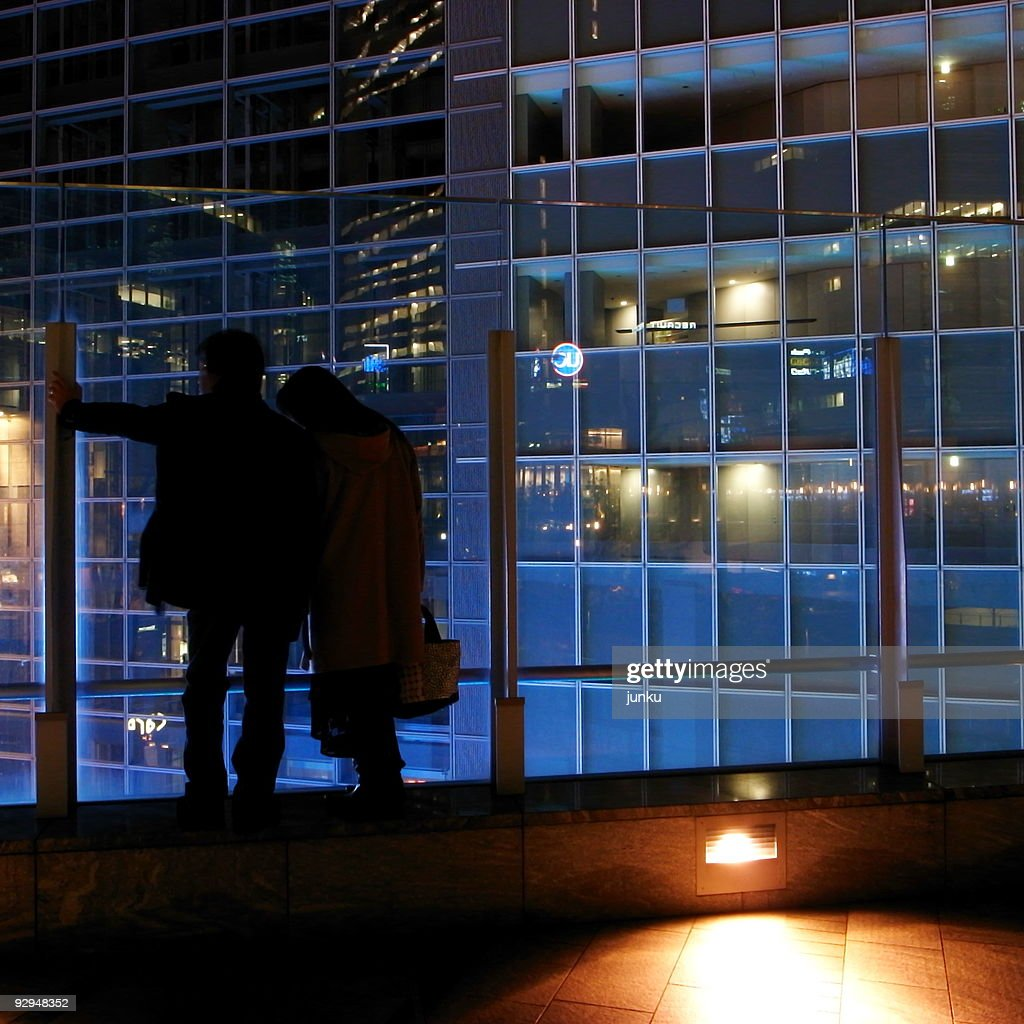 Silhouette couple standing on balcony at night stock photo