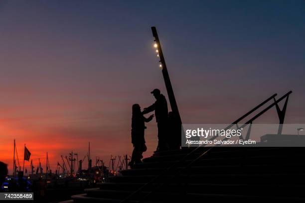 Silhouette Couple Standing On Steps At Harbor Against Clear Sky During Sunset
