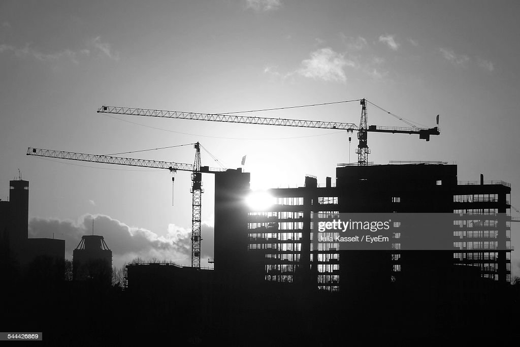 Silhouette Cranes And Buildings Against Sky