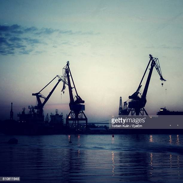 Silhouette cranes and river during sunset