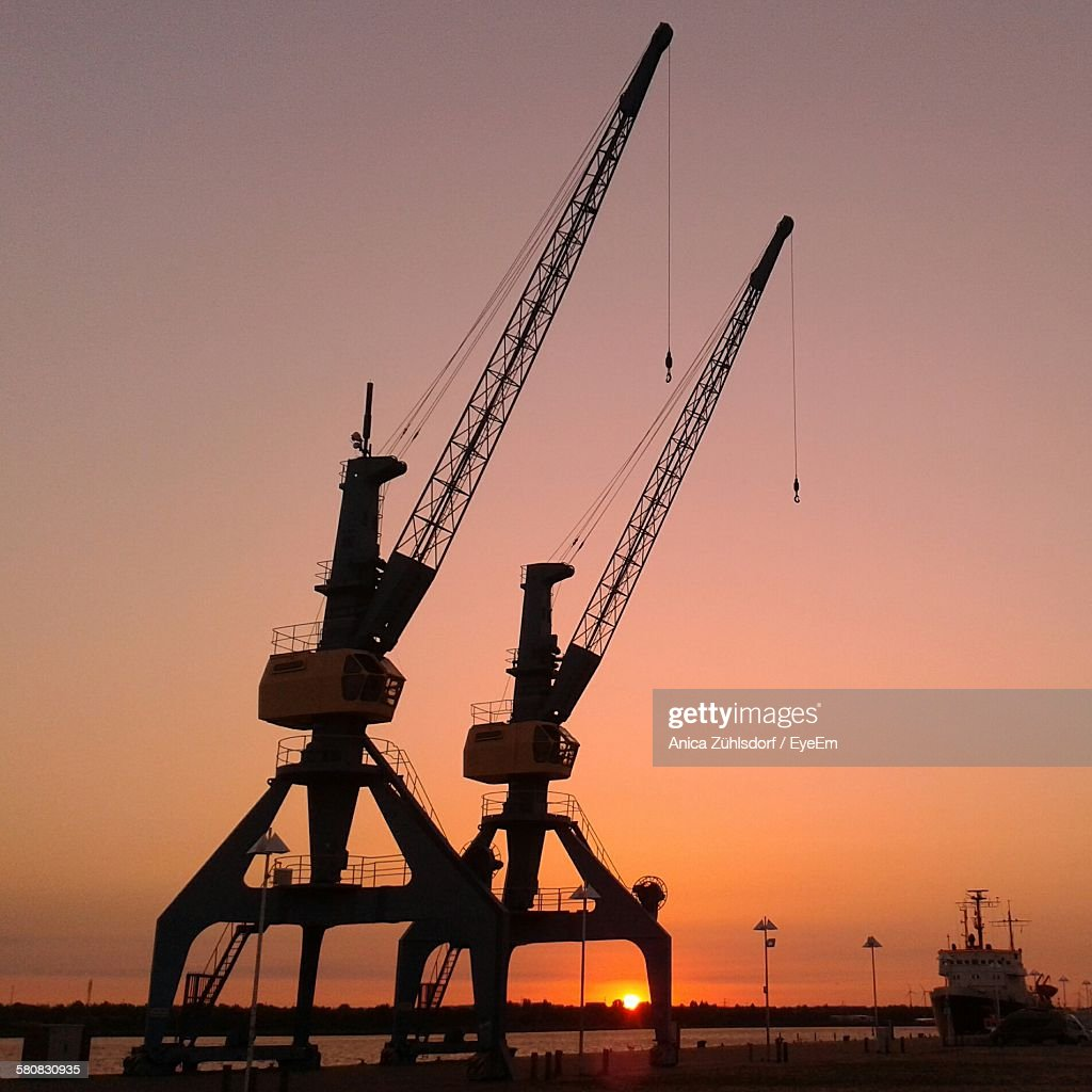 Silhouette Cranes At Commercial Dock Against Sunset Sky