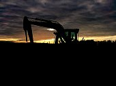 Silhouette Earth Mover On Field Against Cloudy Sky