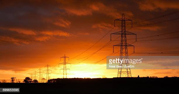 Silhouette Electricity Pylons Against Cloudy Sky At Sunset