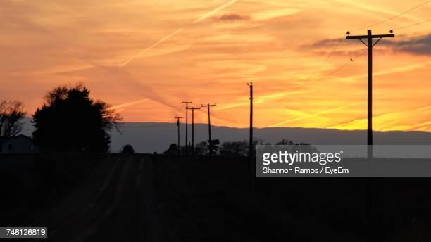 Silhouette Electricity Pylons On Field Against Cloudy Sky During Sunset
