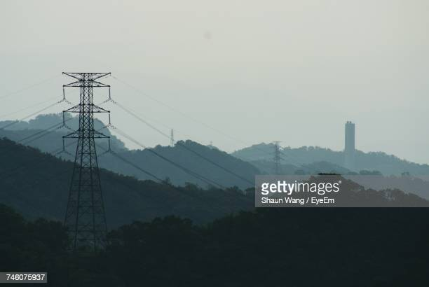 Silhouette Electricity Pylons On Tree Mountains During Foggy Weather