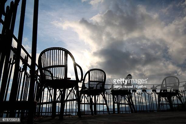 Silhouette Empty Wooden Chairs At Balcony Against Cloudy Sky