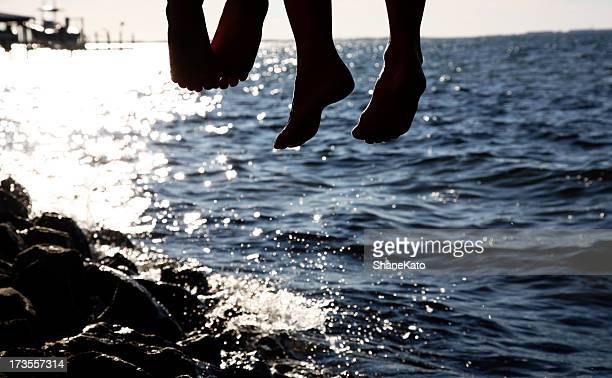 Silhouette Family Feet hanging from a Dock at the Bay