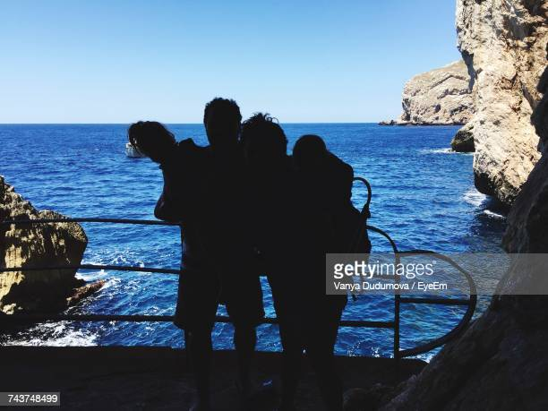 Silhouette Family Standing On Cliff Against Sea During Summer