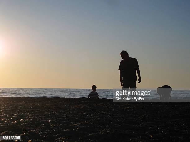 Silhouette Father Standing By Sons At Beach Against Clear Sky During Sunset