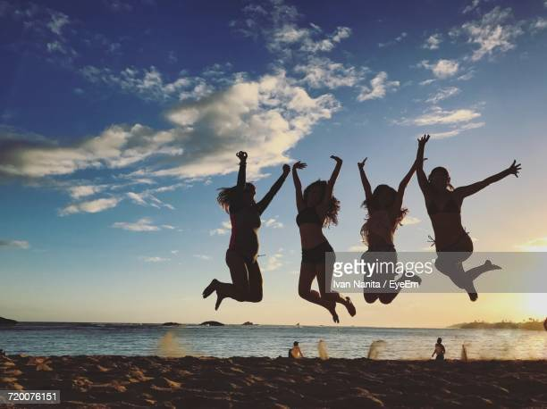 Silhouette Female Friends Jumping On Sand At Beach