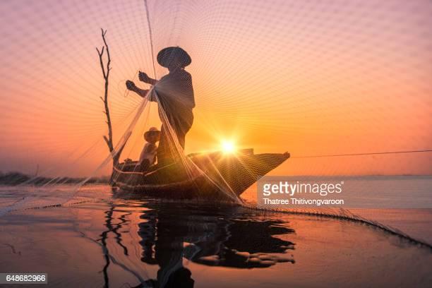 silhouette fisherman at sunrise of Bangpra Lake in action when fishing, Thailand