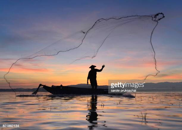 Silhouette Fisherman boat in action at sunrise ,Thailand.