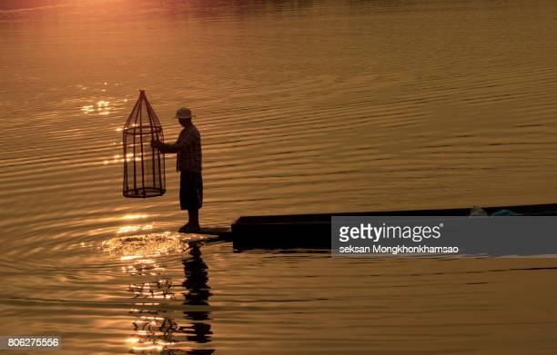 silhouette fisherman of Bangpra Lake in action when fishing, Thailand