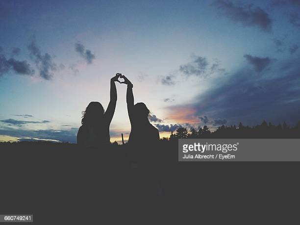 Silhouette Friends Making Heart Shape From Hands Against Sky