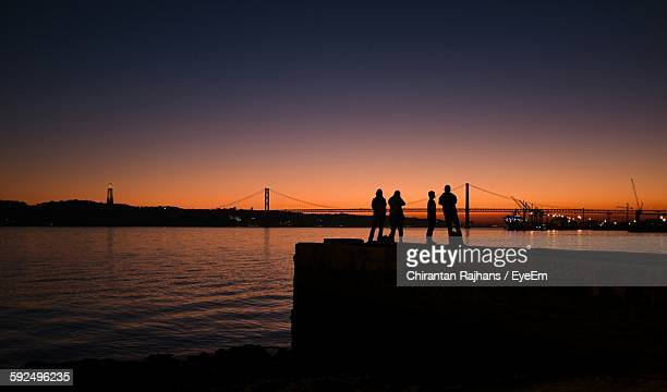 Silhouette Friends On Pier By Tagus River Against Orange Sky
