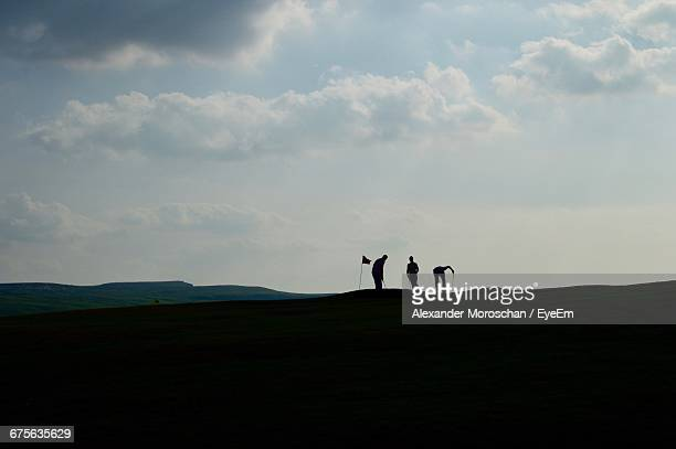 Silhouette Friends Playing Golf On Field Against Sky