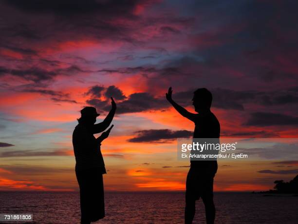 Silhouette Friends Standing At Beach Against Cloudy Sky During Sunset