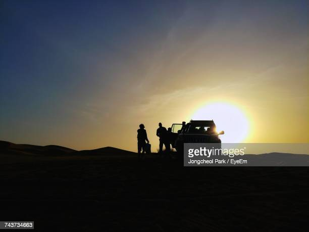Silhouette Friends With Off-Road Vehicle At Sahara Desert Against During Sunset