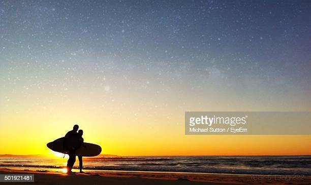 Silhouette friends with surfboard standing at shore on beach during sunset