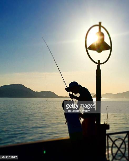 Silhouette Girl And Parent Fishing In Lake During Sunset