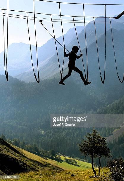 Silhouette girl climbing rope