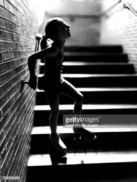 Silhouette Girl Wearing Roller Skate Looking Up While Standing On Steps