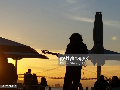 Silhouette Guitarist Playing Guitar At Cafe By Bridge Against Orange Sky