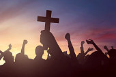 Image of silhouette hand holding christian cross, with people background