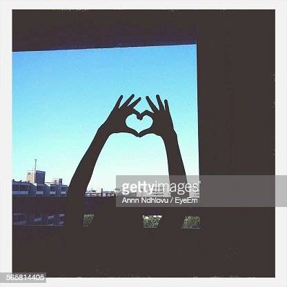 Silhouette Hand Making Heart Shape Against Blue Sky