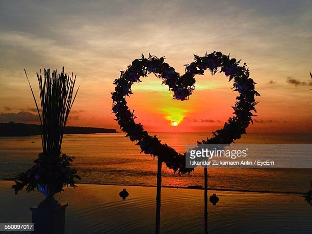 Silhouette Heart Shape Wreath On Beach During Sunset