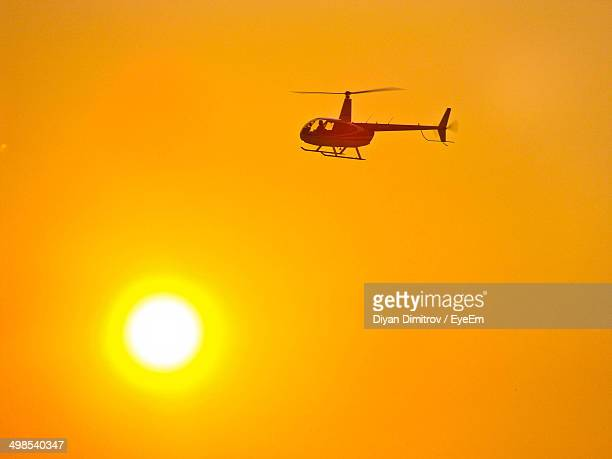 Silhouette helicopter against orange sunset