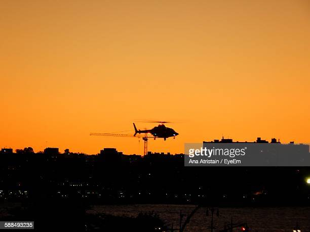 Silhouette Helicopter Over Cityscape Against Clear Sky At Sunset