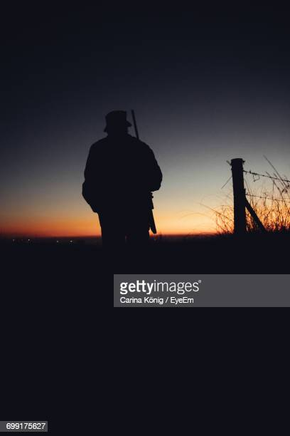 Silhouette Hunter With Rifle Standing On Field During Sunrise